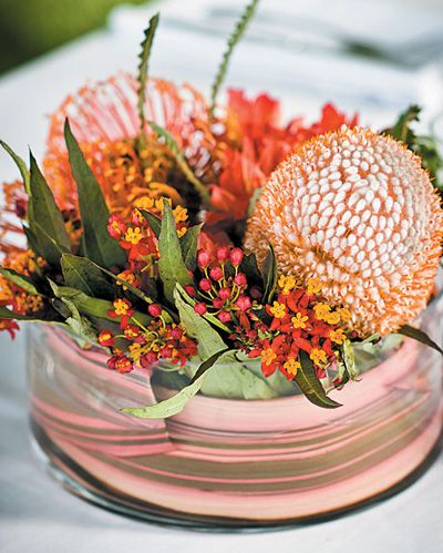 Proteas, Dahlias, and Flax Grasses   Photo: Lisa Monahan Photography I love a brightly colored centerpiece with unique blooms for a wedding with a whimsical theme (like Kathleen and Joshs carnival-themed wedding). This centerpiece by Pot & Box features a gorgeous mix of proteas, banksias, asclepias, dahlias, and flax grasses. Its vibrant red-and-orange hue paired with its interesting shape make this arrangement bold enough for a wedding with uniqu