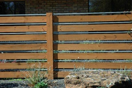 Place the boards horizontally and alternate them with aluminum pipe. I like that the fence still provides privacy without being overbearing and unfriendly; there are spaces for vines to grab hold as well. Beautiful, clean and contemporary!
