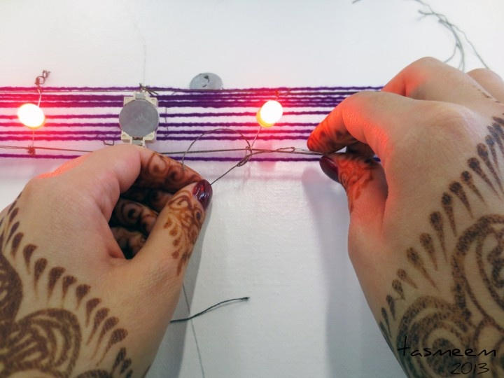 Tasmeem 2013 - eTextiles with Lynne Bruning  at VCU Qatar and Mathaf  Museum.  Handweaving with conductive thread, LEDs and 3V batteries.  Lowla secures a 10mm red LED into the warp.