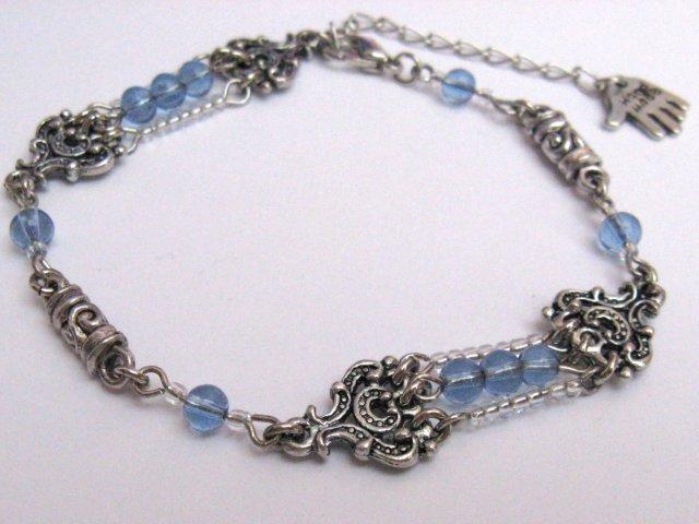Armbandje gemaakt van glas kralen en metalen fantasie ornamentjes.