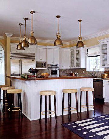 A nautical theme drove the kitchen design. Brass pendants from Circa Lighting hang above a beaded board island with a waxed teak top.