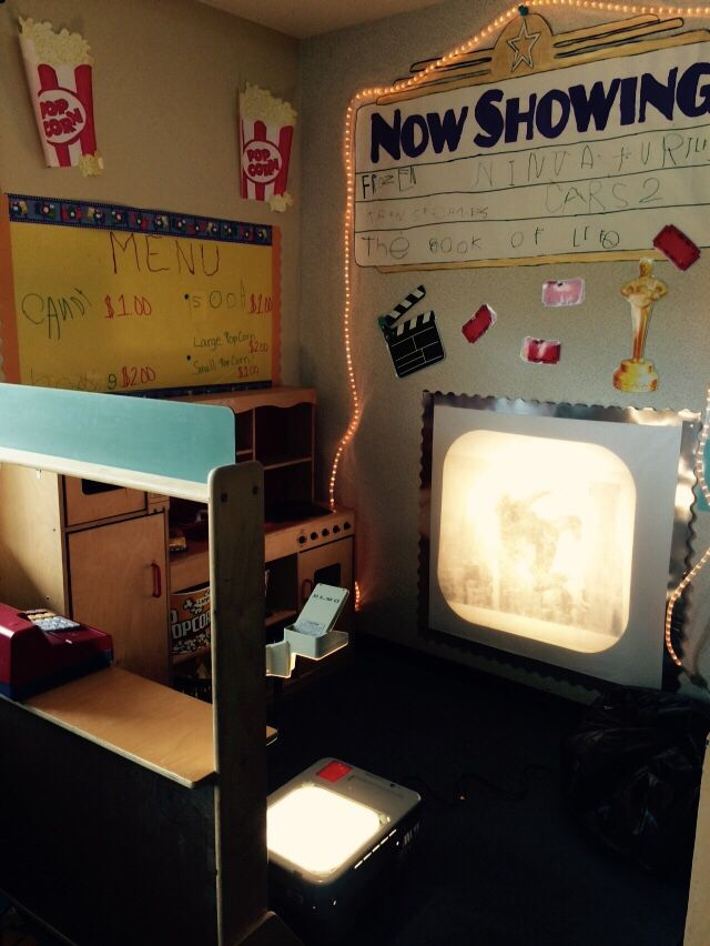 Movie theater in the Dramatic Play center. Kids sell popcorn, candy, drinks and movie tickets and use the projector to show images from their favorite movies.