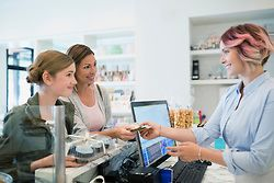 Mother and daughter paying worker in bakery