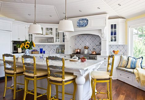 Waterfront House Remodel.  The kitchen's unusual shape prevented both an eating area and a working island, so they opted to combine the two. The white marble island top gets a sunny lift from French bar stools painted in blue and yellow and cushioned with checks of yellow and white.
