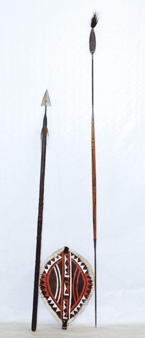 Lot 102: African Spear and Shield Assortment; Three unmarked items including a painted hide and animal fur shield, a carved wood iron spear and a wood, iron and fur spear with incised decoration on the pole