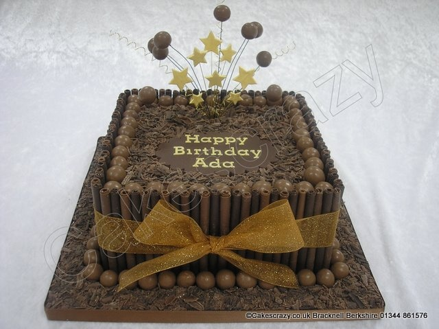 Malteser Cake. Square chocolate celebration cake decorated with milk and plain chocolate rolls tied together with a chiffon ribbon, and Maltesers. Covered with flakes of crumbled chocolate and finished with Malteser explosive starburst topper