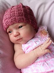 Seventh is a free pattern written for 8ply/DK weight yarn, to fit a newborn babe, with an approximate head circumference of 30cm, 32.5cm, or 35cm (3 sizes). This hat is constructed from the brim upwards, and is knit in the round. It features a very simple textured stitch, that will work well for solid, semisolid, or variegated yarn. The crown of the hat is finished without having to incorporate the textured stitch into crown decreases.