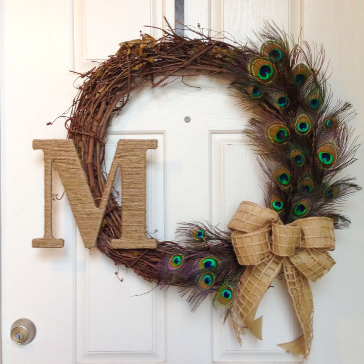 peacock feather vine wreath with an initial...I would leave the initial off and change the bow color