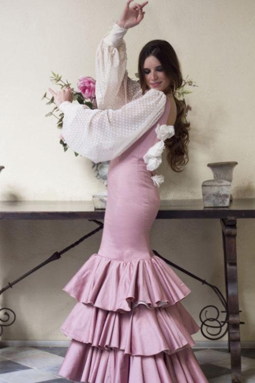 Traje de flamenca Jazmín color rosa maquillaje, con amplias mangas de plumeti beige y escote en espalda adornado con flores de jazmín elaboradas a mano.