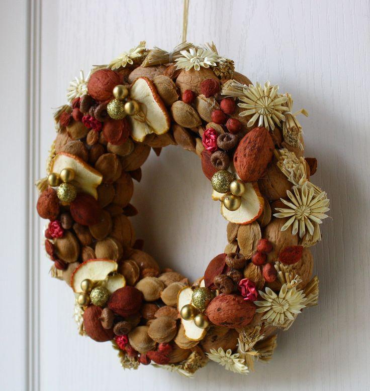 Vítací věnec přírodní se zlatem Ozdobný věnec z přírodních materiálů je barevně laděn do teplých podzimních tónů s náznakem přicházejících vánoc. Je vyroben ze skořápek oříšků, pecek, trávy, slámy, sušených jablíček, malých žaludů a lýka. Doplněn zlatými kuličkami. Upevněn je na pevném slaměném korpusu. Korpus je obalen recyklovaným papírem. Ze ...