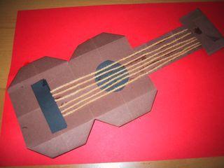 vouw 16 vierkantjes . Precies in het midden knip je aan twee kanten 1 vakje in. vouw dan de hoekjes naar binnen. Je hebt nu een rockgitaar. Als je liever een gewone gitaar wilt, dan vouw je de puntjes nog even en naar binnen. een gitaar heeft 6 snaren, dus van wol, knip je 6 touwtjes die even lang zijn. Knip nog wel even een rondje voor het gat. De hals van de gitaar maak je heel makkelijk door gewoon een strook van 16 vierkantjes af te knippen. Of laat je kinderen zelf een hals knippen uit…