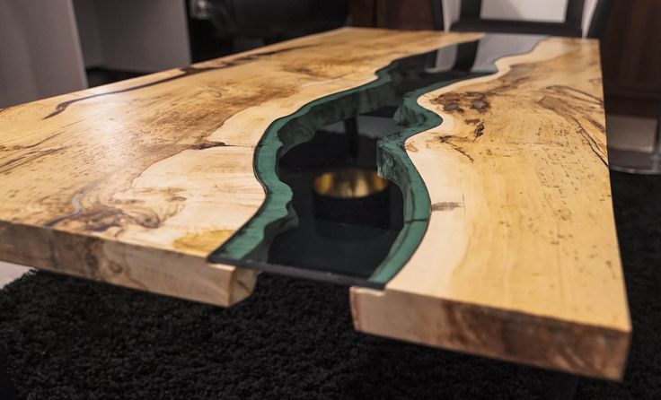 Handmade River Coffee Table made of old solid timber. Blue transparent glass. Filled with epoxy resin. Legs made of metal coated with mat black colour.  It's unique, one of a kind solid piece of wood. The resin that fills the gaps glow in the dark. The unique combination of tree rings to bring out the effect of the variety of colors.  Dimensions: 145x72cm and 47cm height