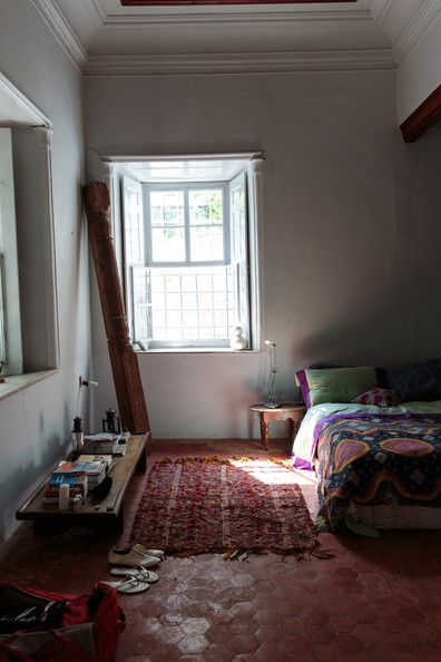 Bohemian - Hexagonal floor tiles and a low bench in a bedroom