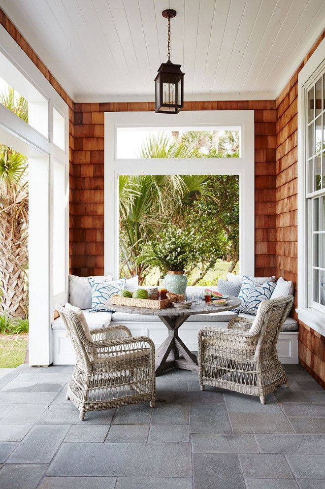 The porch features a gray stone flooring, a custom banquette and one of my favorites outdoor furniture – Kingsley-Bate.