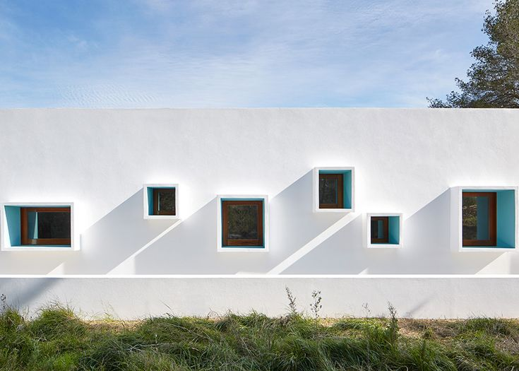 Ca na Maria is a bright white Ibiza home with an assortment of protruding windows.