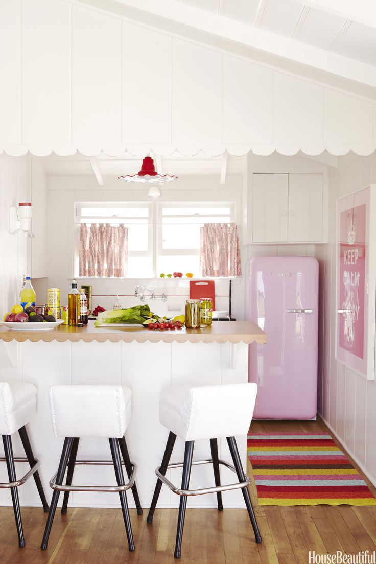 """A pink Smeg refrigerator from Sears is the showstopper in the guest-suite kitchen of a Balboa, California, beach house. """"How about that pink fridge? Isn't it great? It's tiny — perfect for a small kitchen,"""" designer Krista Ewart says. Lina rug from Plastica. Victoria Pearson  - HouseBeautiful.com"""