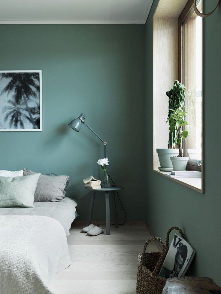 Modern bedroom with green walls and a bedside table with a small lamp.