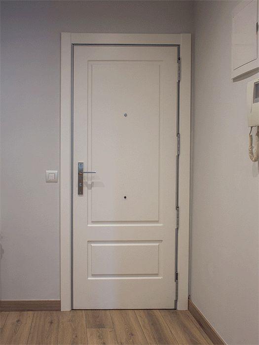 Puerta blindada, el interior es lacado en blanco con molduras y el exterior es de madera natural, siguiendo el diseño del resto de puertas de los vecinos.