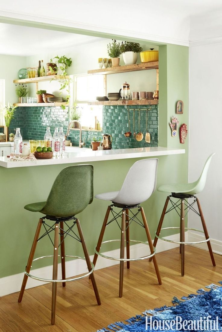 """Justina Blakeney brings her signature flair for bold color to the kitchen of her Los Angeles home. Her breakfast bar and kitchen are painted in shades of green that are true to her """"Jungalow"""" aesthetic. See more green paint colors for every room at HouseBeautiful.com."""