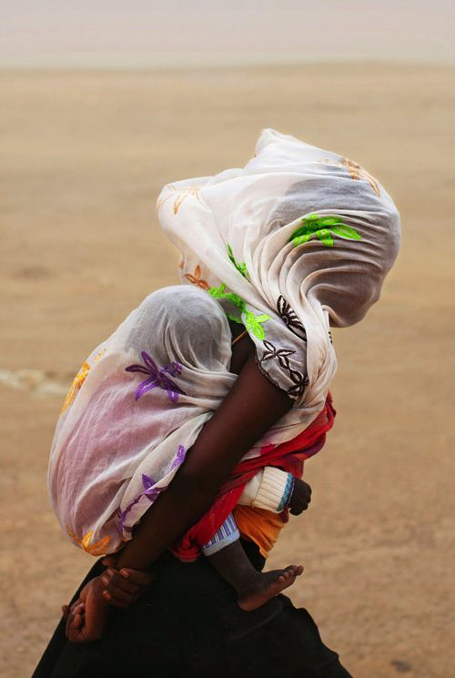 Africa | Woman carrying her child with protection from a sandstorm, Timbuktu, Mali