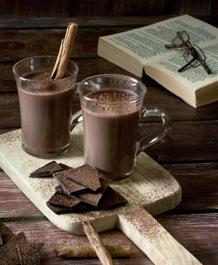 rich hot chocolate in a porcelain mug surrounded by chocolate and cinamon