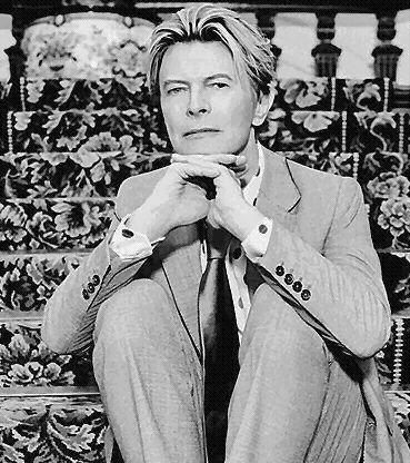 David Bowie in a suit, cufflinks and tie