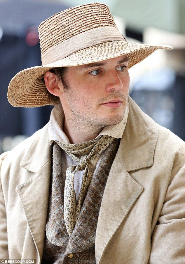 Hat's alright! The 29-year-old looked every inch the part for the period drama, as he dressed up in a long beige trench coat and matching straw hat