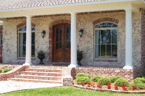 Raised Porch with Brick Pavers and croker sack paint application on French design. By AAA Homes of MS, LLC.