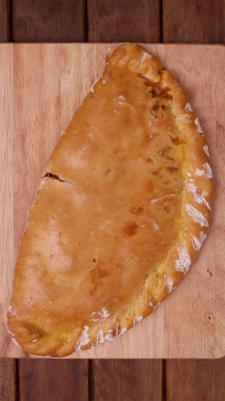 Receita com instruções em vídeo: Esse calzone de pizza é o prato perfeito para dividir com a família e os amigos!  Ingredientes: 2 colheres de sopa de extrato de tomate, 150g de linguiça calabresa cortada em rodelas, 1 cebola cortada em tiras, 100g de queijo muçarela ralado, 1 pitada de sal, 1 pitada de orégano, 6g de fermento biológico seco, 1 colher de chá de azeite de oliva, ¾ de xícara de água, ¼ de xícara de leite, 1 pitada de açúcar, 250g de farinha, 1 pitada de sal
