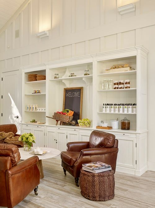 A modern farmhouse style room at the spa at Farmhouse Inn designed by Myra Hoefer. White board and batten walls, brown leather club chairs, and soaring ceiling.