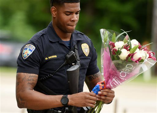 (Henrietta Wildsmith/The Times via AP). Baton Rouge Police Department Officer Markell Morris holds a bouquet of flowers and a Superman action figure that a citizen left at the Our Lady of the Lake Hospital where the police officers were brought this mo...