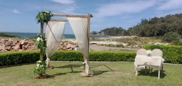 Rustic wooden wedding canopy with florals and natural linen