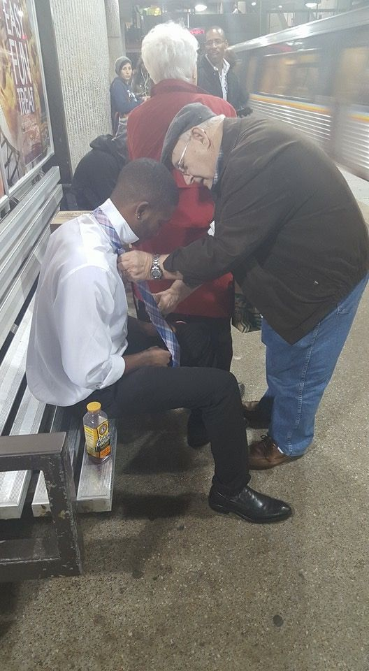 """The young guy sitting down was struggling with his tie. The woman in the red coat noticed & asked 'Do you know how to tie it properly?' The young guy said 'No ma'am.' She taps her husband & says 'Come to this side & teach this young man how to tie his tie."""" The older gentleman moved without hesitation & gave him a step-by-step tutorial; then – afterward – the elder gentleman watched the young gentleman repeat the steps and show him that he had it. #FaithInHumanity Good Deeds #Kindness"""