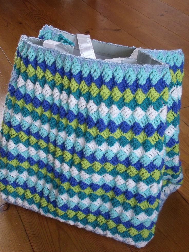 Vierkantjes gehaakt in een ruitjespatroon en daarna om een stevige boodschappentas gedaan en bovenaan vastgenaaid met een omslagsteek.