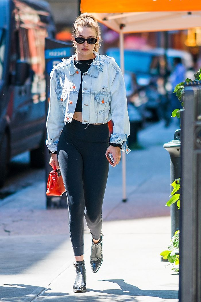 4c6498ea341 Treggings  Gigi Hadid wearing thick black leggings with a denim jacket and  ankle boots