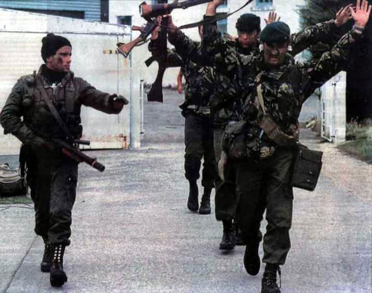 Comando Anfibio Jacinto Eliseo Batista de la Infantería de Marina, agrupación de élite que hiciera el desembarco el dia 2 de abril de 1982 y tomara las Islas Malvinas. Portando una ametralladora Sterling con silenciador con la mano derecha y varias granadas mientras con el otro brazo ordena a tres prisioneros ingleses con las manos en alto, rendidos en aquella fria mañana.