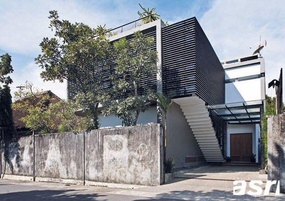 Bidang secondary skin dari rangka besi, sirip-sirip alumunium dan bilah kayu ini seolah-olah membungkus ruang dalam rumah baru sehingga tampil kontras dengan rumah tua di sebelahnya.