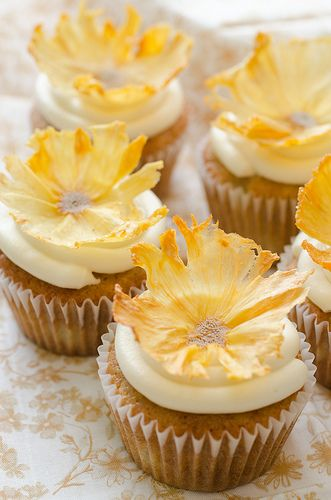 Cupcakes with Pineapple Flowers - such a pretty and clever decoration: Slice some pineapple really thin and bake low and long in the oven, pop them in cupcake tins overnight to give them the shape!