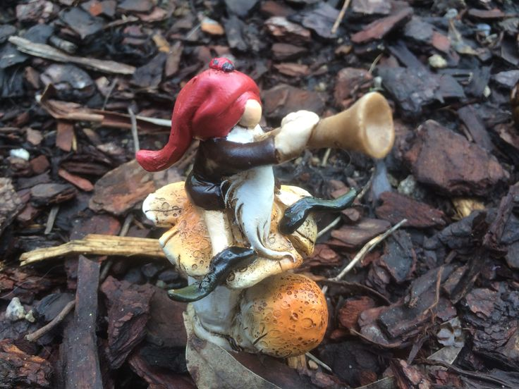 Garden gnome playing a horn on a toadstool