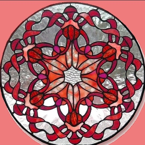 Lots of free stained glass patterns.  Like this one a lot.  I'd probably introduce a lot more colors to it, though, to make it resemble a rose window in a cathedral.