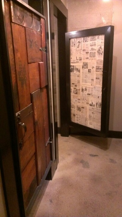 Recycled 19th century shipping crates and news print doors for public restroom - By Andrew Yetter lovedesignco.com