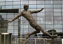 Emlyn Hughes (England, 1969–1980, 62 caps, 1 goal) and (Liverpool FC, 1967–1979, 474 apps, 35 goals) has been immortalised in a bronze statue of Hughes in mid-kick and was unveiled on 18 April 2008 in his home town of Barrow, Cumbria. The former England and Reds captain died at the age of 57 on 9 November 2004. The defender was awarded an OBE in 1980, played 650 games for Liverpool, won 62 England caps and captained his country 23 times.