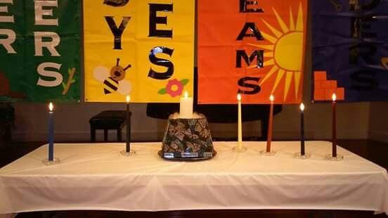 Altar con la vela blanca y las velas del color de cada clase