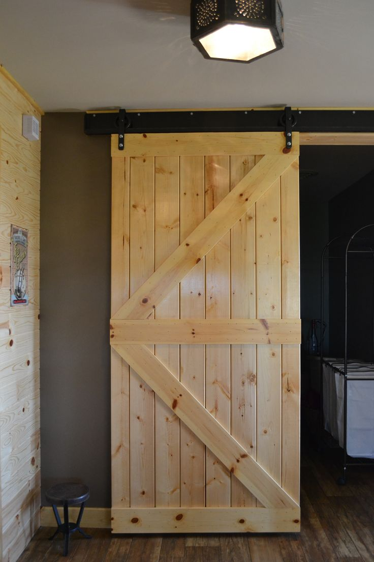 "barn door created out of our left over knotty pine boards. the track was fabricated at a local welding shop and painted flat black. needs a fun handle :) i will warn you, this door is cute but NOT very funcational as it's very heavy and doesn't seal to keep noise out. i suggest if you incorporate one into your floor plan design, it needs to be for ""looks"" where you don't plan on closing it often."