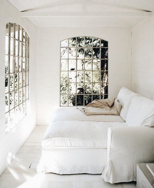 Sitting room   White slipcovered lounging chaises and arched  windows.