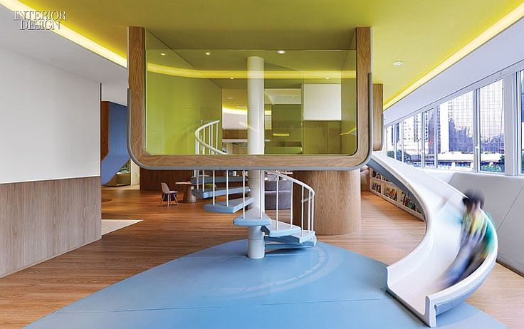 """At Spring Learning, a preschool in Hong Kong, the centerpiece of the lunchroom is a structural column styled as a """"tree house"""" with a slide."""