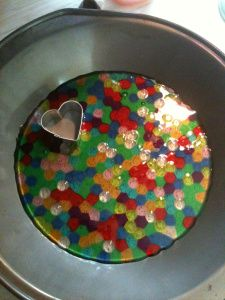 First sun-catcher - SUMMER ACTIVITY! beads. You dump them into a round non-stick cake pan in a SINGLE layer, no greasing necessary and bake them in the oven on 400 for about 20 minutes.