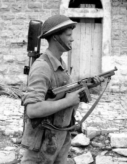 Corporal E.H. Pruner of The Hastings and Prince Edward Regiment, carrying a PIAT anti-tank weapon and a Thompson sub-machine gun with a short box magazine, Motta, Italy, 2 October 1943. (Library and Archives Canada Photo, MIKAN No. 3229941)