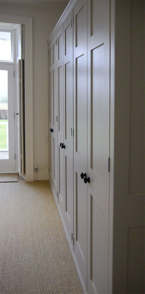 A bank of fitted wardrobes, hand made and painted in Farrow and Ball, Elephant's Breath for a beautiful home in Cumbria.