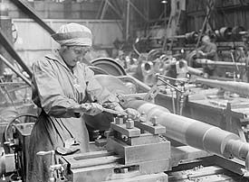 Women at work during WWI in the north east of England. A female war worker adjusts a turning machine in this photo. ©  Imperial War Museum Q20066